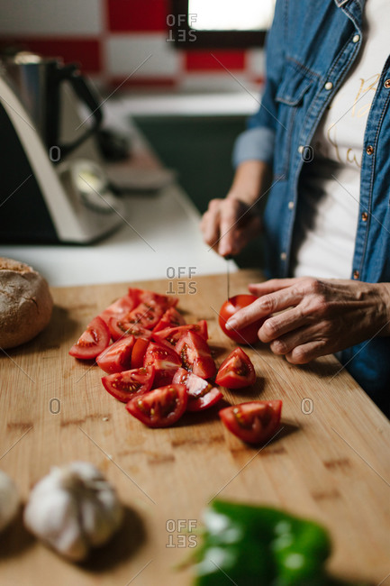 Close-up view of a middle-aged woman's hands chopping some tomatoes