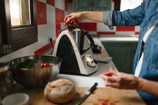 Unrecognizable woman using a kitchen robot for cooking some typical Spanish food