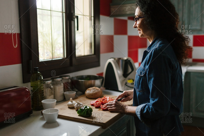 A woman smiles while she's looking throw the window and chopping vegetables for cooking.