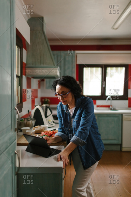 Woman reading some tips about a recipe in a tablet