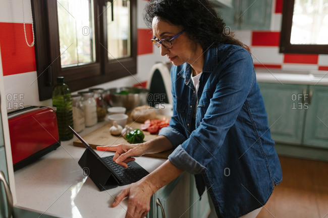 Middle-aged woman using a tablet for cooking in the kitchen