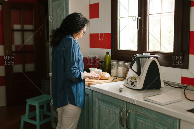 Woman preparing some ingredients to cook with a kitchen robot