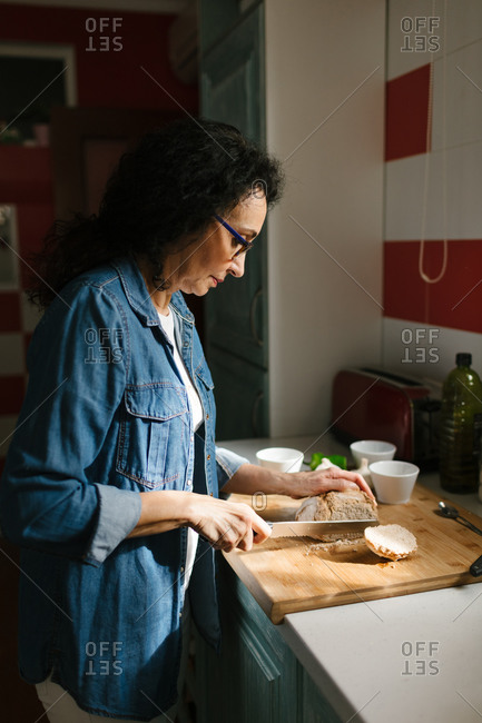 Side view of a woman cutting bread in the kitchen