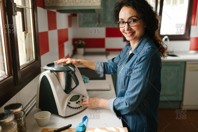 Smiley middle-aged woman cooking with a kitchen robot