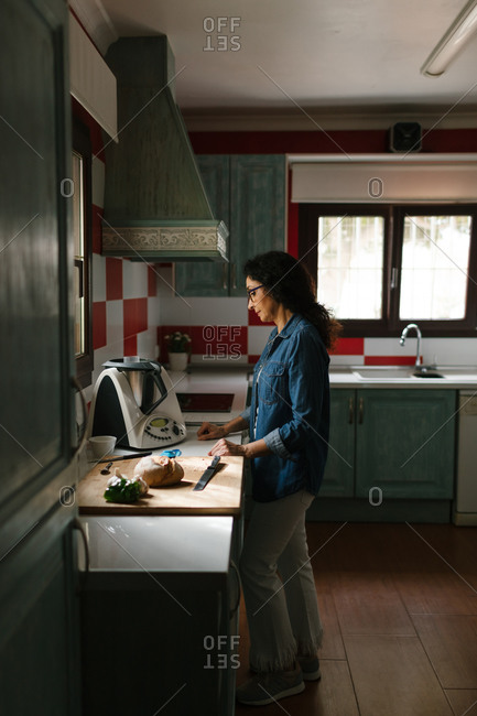 A middle-aged woman is waiting the recipe to be ready because she is cooking with a kitchen robot