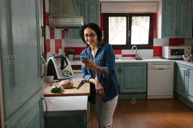 Happy middle-aged woman using a smartphone while she is waiting for the Kitchen robot to finish.