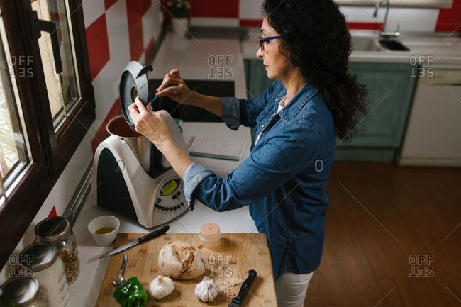 Middle-aged woman introducing a few ingredients in the Kitchen Robot