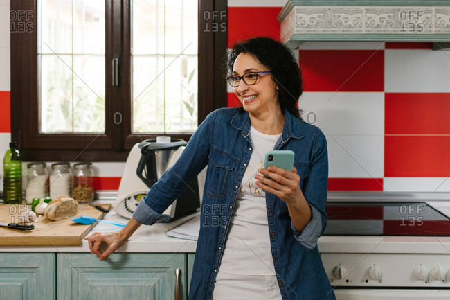 Happy beautiful woman with a smartphone in the kitchen