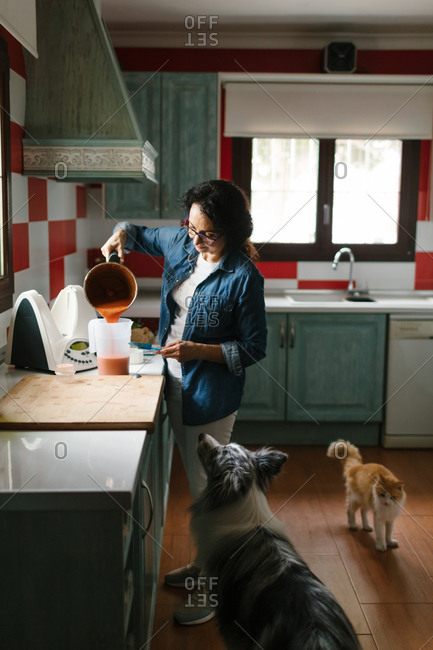 Woman serving a meal in the kitchen while her pets are looking to the food.