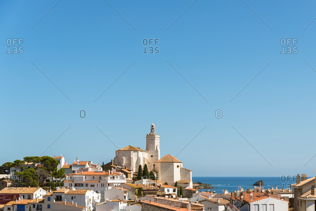 Picturesque view of old small Cadaques town located on bay of Mediterranean sea in sunny summer day with calm blue water