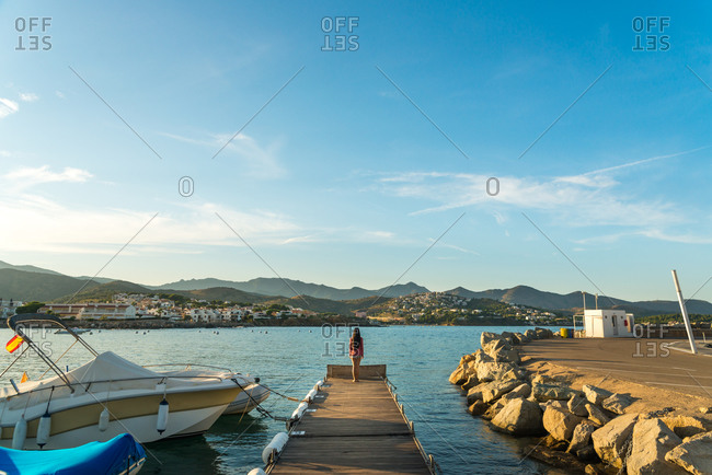 Back view of unrecognizable female traveler standing on wooden pier near vessels and admiring picturesque view of small Llanca municipality with buildings and cloudy sky reflected in calm water in sunny day in Spain
