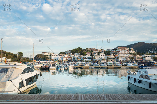 Wooden pier near vessels and picturesque view of small Llanca municipality with buildings and cloudy sky reflected in calm water in sunny day in Spain