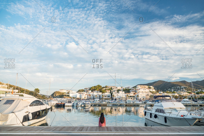 Back view of unrecognizable female traveler sitting on wooden pier near vessels and admiring picturesque view of small Llanca municipality with buildings and cloudy sky reflected in calm water in sunny day in Spain