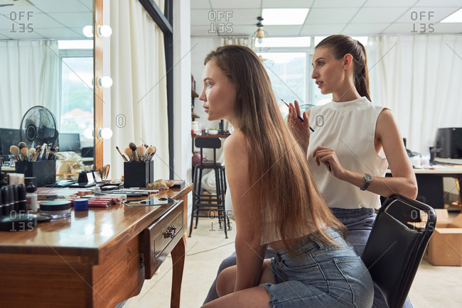Positive young female makeup artist with brush standing near attractive client looking in mirror and checking makeup in modern studio