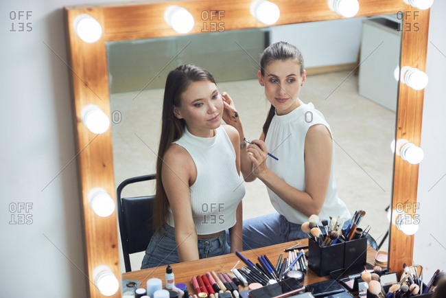 Positive young female makeup artist doing clients face makeup using brush looking at cozy big mirror with lights in contemporary beauty salon