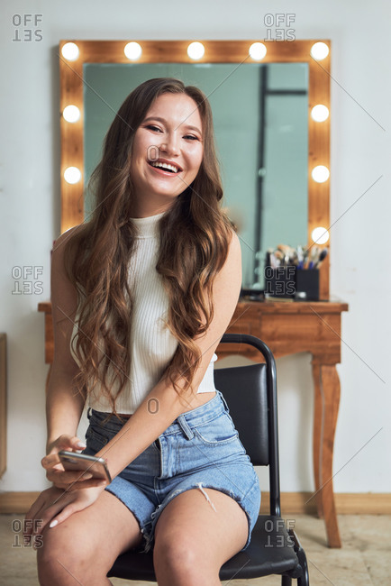 Positive stylish beautiful woman sitting gracefully on chair against cozy vanity table and mirror with lights while looking at camera sensually