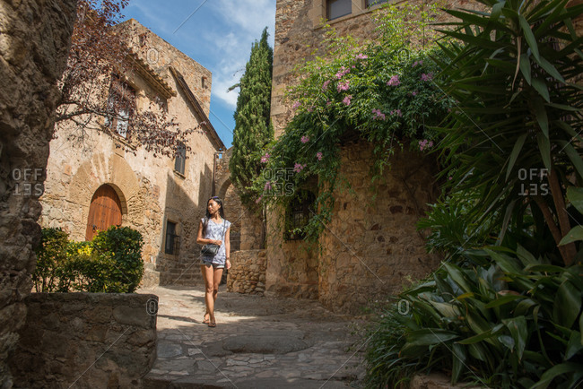 Young ethnic female tourist in casual clothes walking on narrow street among ancient stone buildings with green plants while visiting Tossa de Mar municipality in Catalonia in Spain