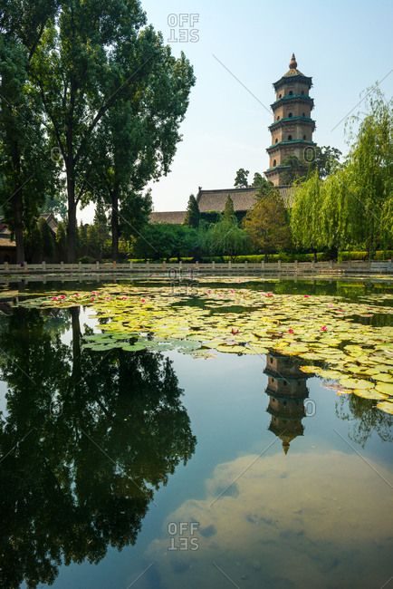 Exterior of oriental temple located in lush garden with lake on sunny day in Shanxi