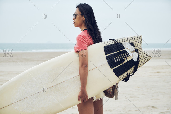 Side view of young Asian female surfer in summer outfit walking on sandy beach and carrying surfboard against calm blue sea looking away