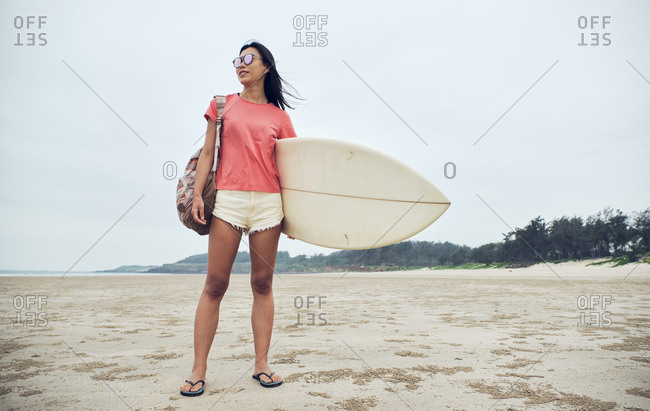 Full length young Asian female surfer in summer outfit walking on sandy beach and carrying surfboard against calm blue sea looking away