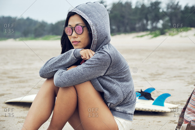 Crop contemplate Asian female in hoodie and sunglasses sitting on sandy beach near surfboard and looking away thoughtfully