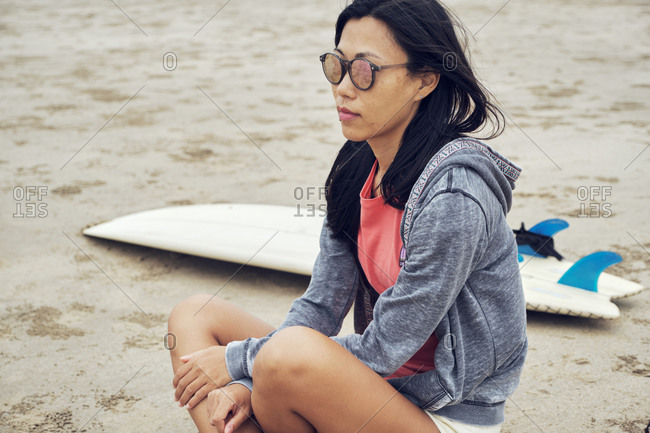 Crop contemplate Asian female in casual clothes and sunglasses sitting with crossed legs on sandy beach near surfboard and looking away thoughtfully