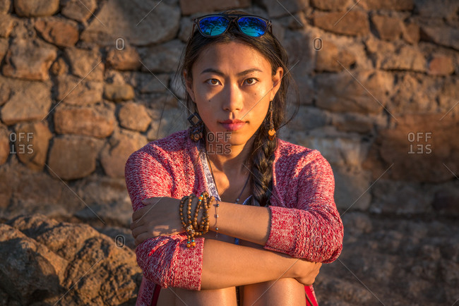 Calm young Asian female in colorful knitted jacket with natural bracelets and earrings looking at camera while sitting against ancient stone wall