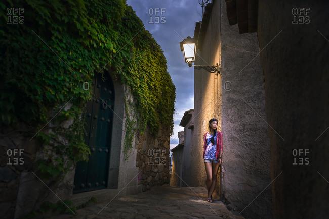 Calm young ethnic female in casual colorful clothes leaning on stone wall of aged building while exploring ancient street of Tossa de Mar municipality in Spain in summer evening