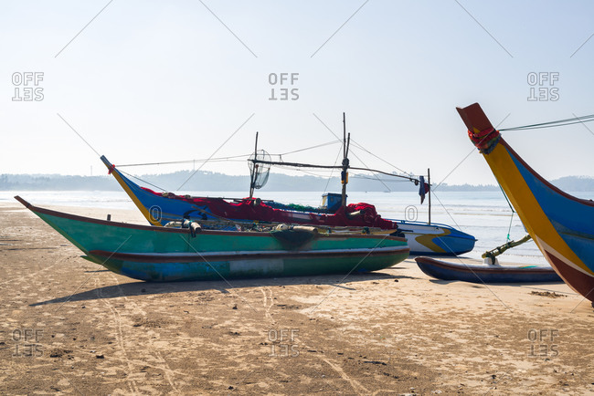 Weathered boats moored on seashore on sunny day on background of cloudless sky