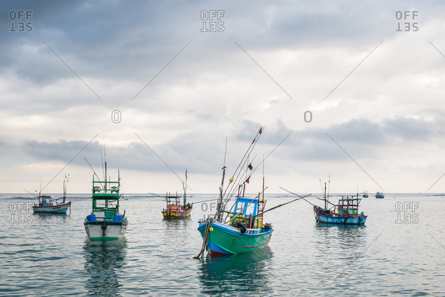 Colorful shabby boats floating on calm water of sea on background of stormy sky