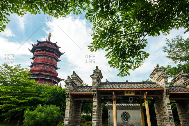 Low angle picturesque view of beautiful ornamental building of traditional Chinese pagoda framed by green tree branches against cloudy blue sky in summer day in Xiamen in China