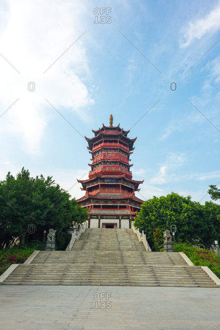 Low angle picturesque view of beautiful staircase of ornamental building of traditional Chinese pagoda framed by green tree branches against cloudy blue sky in summer day in Xiamen in China