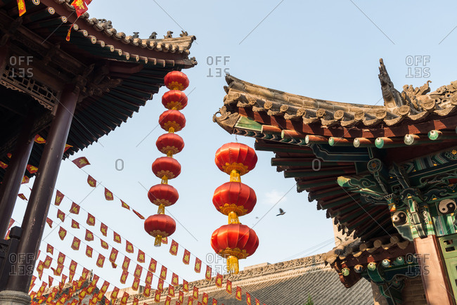 From below of decorative red paper lanterns hanging from curved roofs of Buddhist temples