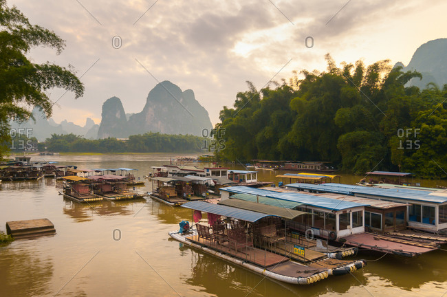 May 15, 2012: Majestic landscape of bay with shabby traditional vessels on background of rocky mountains and amazing sundown in Yangshuo County in China