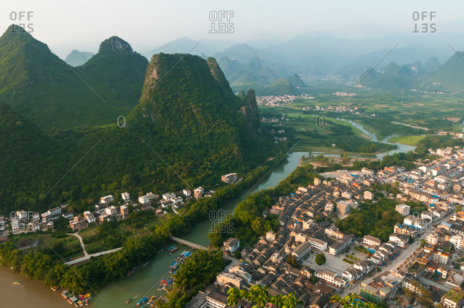 Drone view of settlement with residential houses located in valley and surrounded by green rocks in Yangshuo County, China