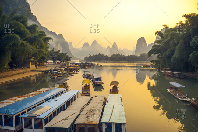 Majestic landscape of bay with shabby traditional vessels on background of rocky mountains and amazing sundown in Yangshuo County in China