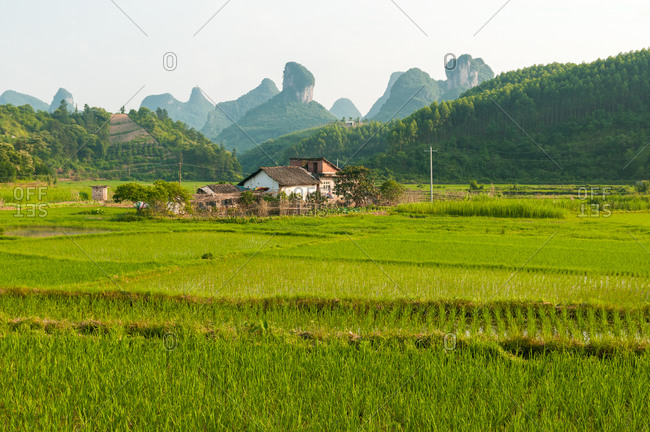 Small cottage located on green field on background of mountains in China