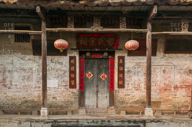 May 19, 2012: Exterior of aged stone building with shabby walls and ornamental doorway with paper lanterns in Yangshuo County