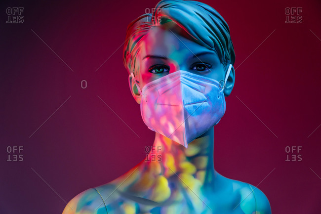 Plastic female mannequin in medical mask illuminated by colorful lights in studio on purple background