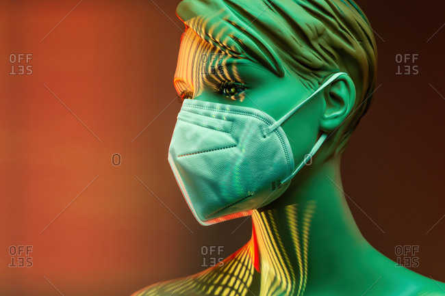 Plastic female mannequin in medical mask illuminated by colorful lights in studio on orange background