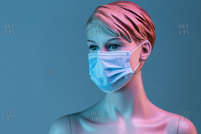Plastic female mannequin in medical mask illuminated by colorful lights in studio on blue background