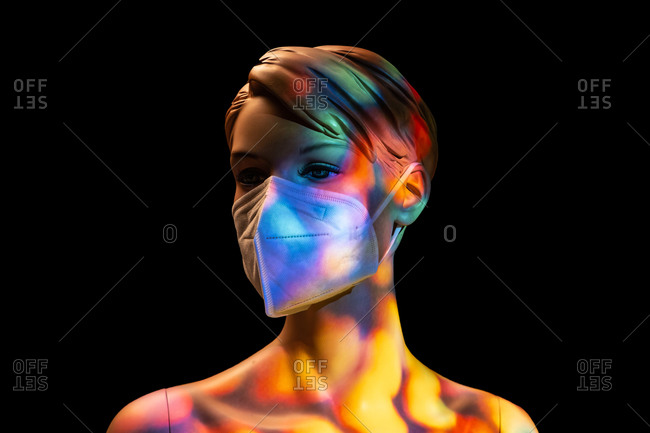 Plastic female mannequin in medical mask illuminated by colorful lights in studio on black background