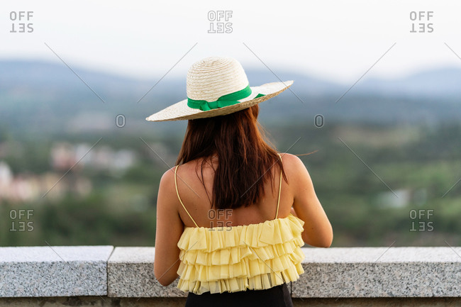 Back view of unrecognizable female in summer dress and straw hat leaning on stone fence admiring blurred background of cityscape
