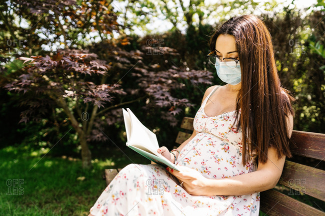 Female in floral dress and medical mask sitting on bench and reading book during epidemic on sunny summer day in park