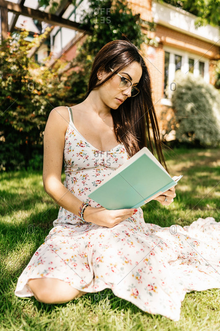 Smart female in floral dress and glasses sitting on green grass in yard and reading interesting book on summer day