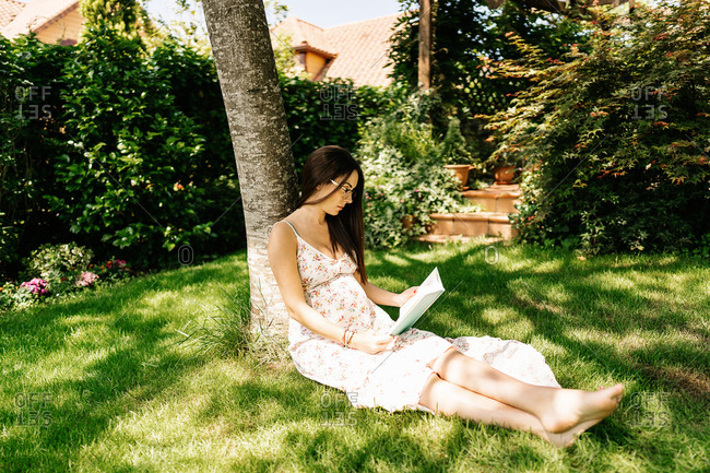 Smart woman in a floral dress and glasses, leaning against a tree and reading an interesting book on a summer day.