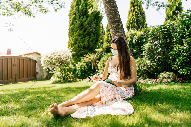 Pregnant female in medical mask, leaning against a tree and reading an interesting book on a summer day.