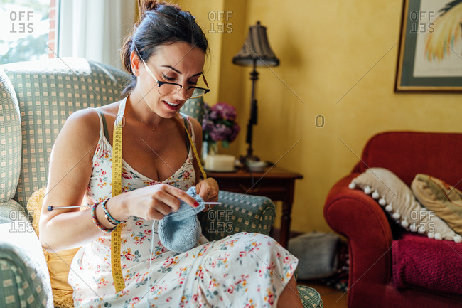 Focused brunette in glasses sitting in comfortable armchair and knitting while resting in cozy room at home
