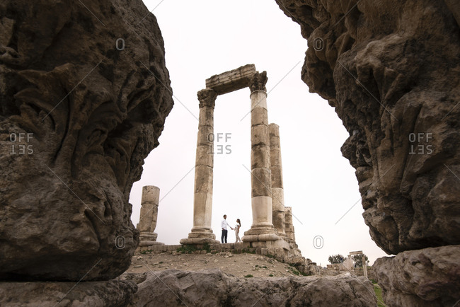Tender couple of tourists standing under stone arch of Amman Citadel during vacation in Jordan