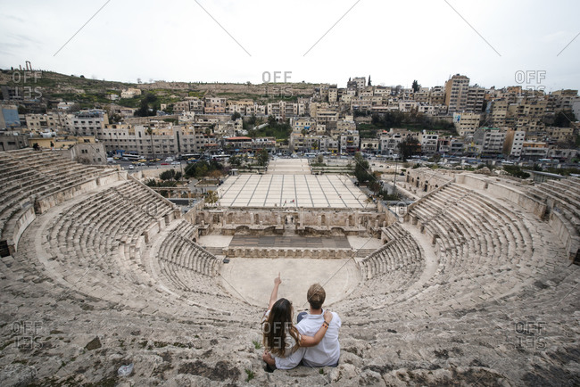 High angle back view of traveling couple sitting on stone stairs of ancient theater in Amman during summer holiday